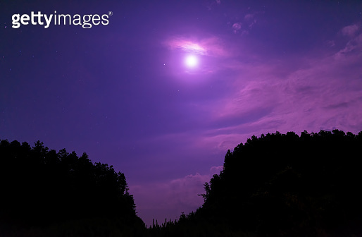 Moon with lunar halo in starry sky