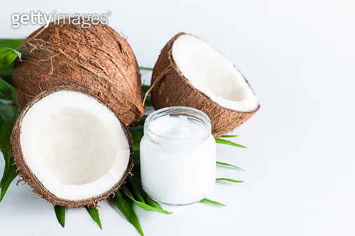 Ripe half cut coconut and cream with green leaves on a white isolated background. Healthcare and medical concept. Skin care.