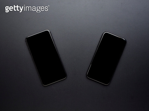 Two black smart phones with blank screen on black background.