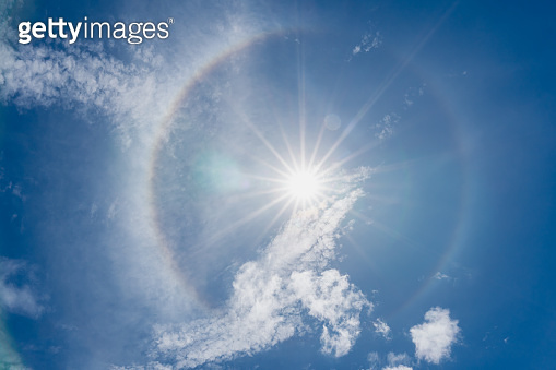 phenomenon sun halo on blue sky with sunbeams and clouds in the day