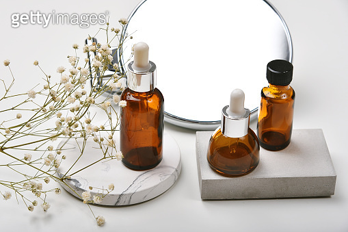 Cosmetic glass bottle containers packaging with product display presentation, Blank label for organic branding mock-up, Natural skincare beauty product and aromatherapy oil concept.