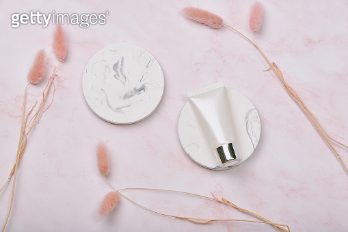 Cosmetic bottle containers on pink marble background, Blank label package for branding mock-up, Natural organic beauty product concept, Research and development of purified skincare.