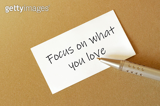 pen, white paper with text Focus on what you love on the brown background