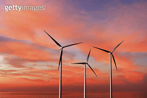 Wind turbines as alternative renewable energy on a background sunset sky.