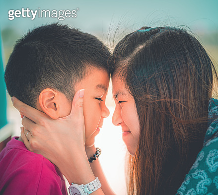 Asian Mother and Son is kissing and hugging for Love and affection and Family togetherness concept