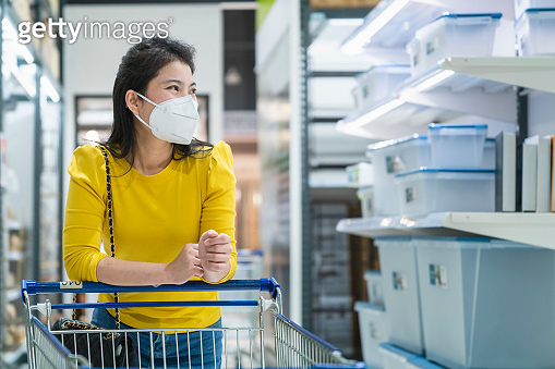 New normal lifestyle asian female yellow dress wear protecting mask shopping in department store after end of lockdown quarantine periodNew normal lifestyle asian female yellow dress wear protecting mask shopping in department store after end of lockdown