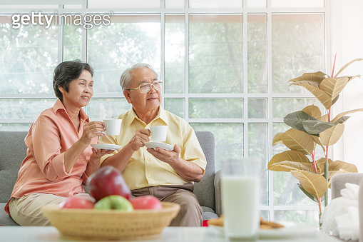 Asian Elderly retired couple looking out the windows and drink hot tea while relaxing at home.
