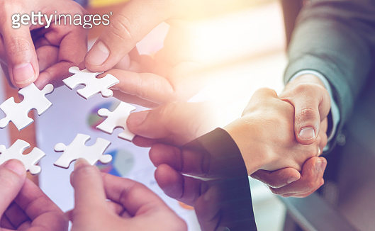 Business team strategy concept with jigsaw and handshaking for business team solution success concept
