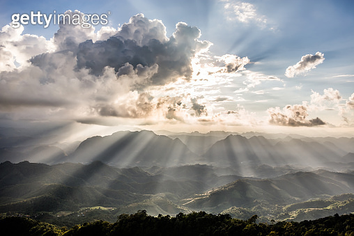 Golden light rays from clouds shining down to mountains.
