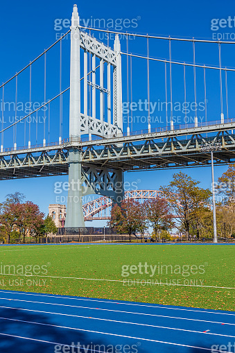 Track and Field Complex and RFK Triborough Bridge with Hell Gate Bridge in background, New York, USA.