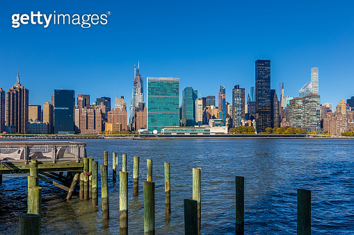 Pier at Gantry Plaza State Park and New York City Skyline with Chrysler Building, UN Building and East River in the Morning.