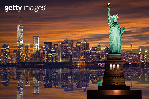 Statue of Liberty and New York City Skyline with World Trade Center and Manhattan Financial District at Sunset.