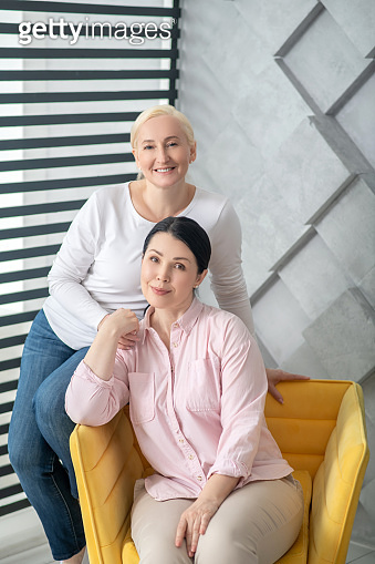 Two adult women in a good mood in a chair.