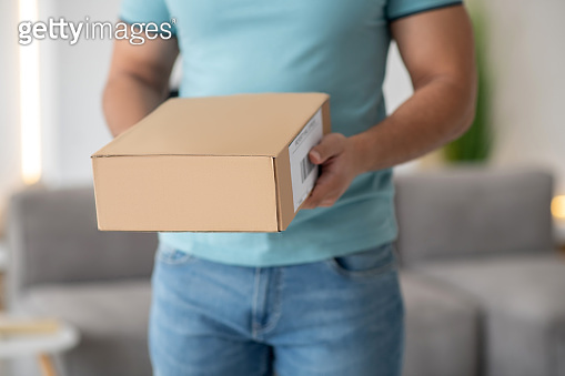 Young male hands holding brown cardboard box