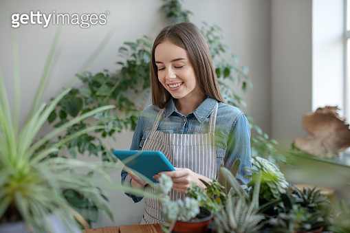 Smiling woman wearing apron taking care of plants