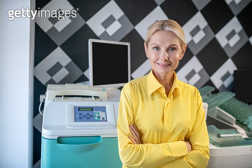 Blonde woman standing in front of printing machine with folded hands