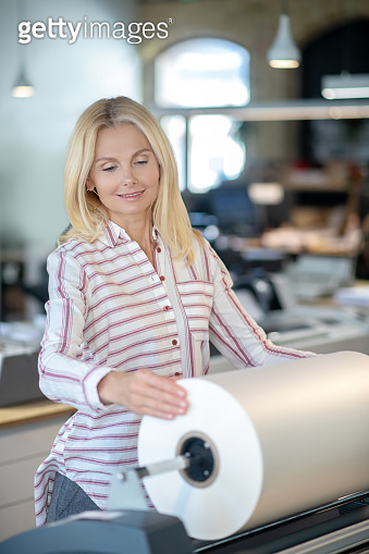 Blonde woman standing at paper roll machine, holding paper roll