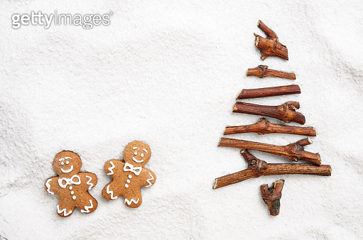Flat lay stylized Christmas tree made of small twigs and gingerbread man cookies on snow background. Space for text