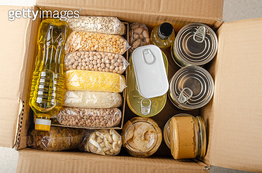 Flat lay view at uncooked foods in carton box prepared for disaster emergency conditions or giving away