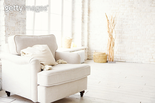 White armchair standing on the floor in front of a window