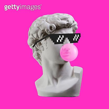 Statue. Earphone. Isolated. Gypsum statue of David's head. Man. Creative. Plaster statue of David's head in pixel glasses. Minimal concept art.