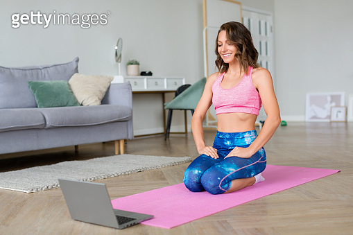 Young woman practices yoga online at home