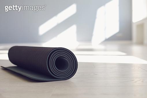 Black yoga mat on the floor of a bright sunny studio.