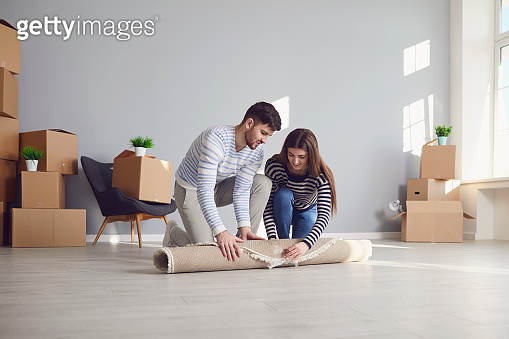 Young couple family with boxes to move in a new house room.