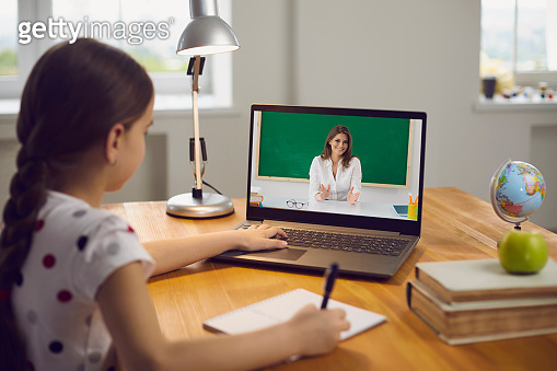 Remote education of children. Little girl watching a video lesson from a teacher course laptop sitting at a table in a living room.