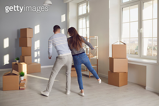 A cheerful couple is playing with a moving box in a bright room of a new house.