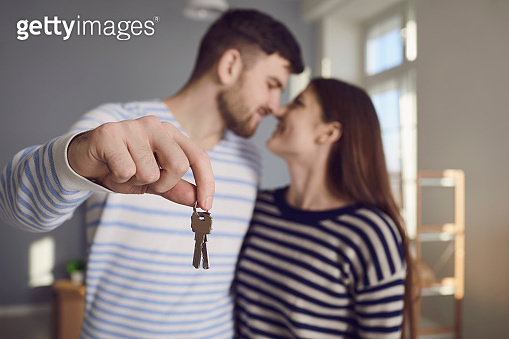 Happy couple with keys to new home in hands smiling while standing in room.