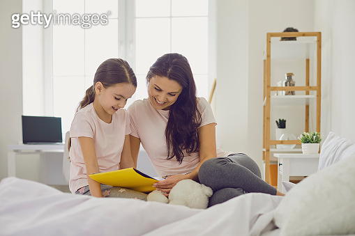 Mother and her daughter girl reading book in bed at home. Parent and child enjoying fairy tale story in bedroom
