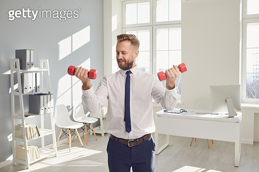Happy successful businessman in a white shirt does exercises with dumbbells in the office.