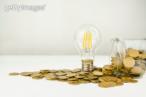 Business concept. Lamp with coins on a light background. Concept of birth of an idea. Business finance concept. Recovery and business growth. Copy space. Banner.
