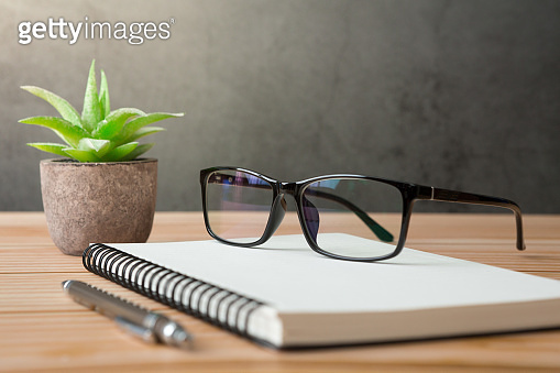 Notebooks, pens, glasses, cactus on wooden desks and loft walls with sunlight and copy space