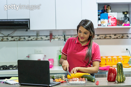 Young woman learning to cook by Youtube video tutorial