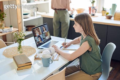 Teenage schoolgirl looking at teacher and several classmates on laptop display