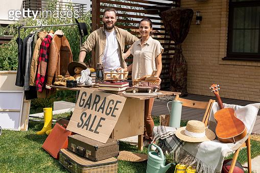Portrait of couple selling garage stuff in backyard