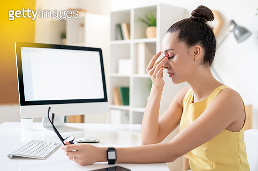 Young tired businesswoman in dress sitting by desk in front of computer monitor
