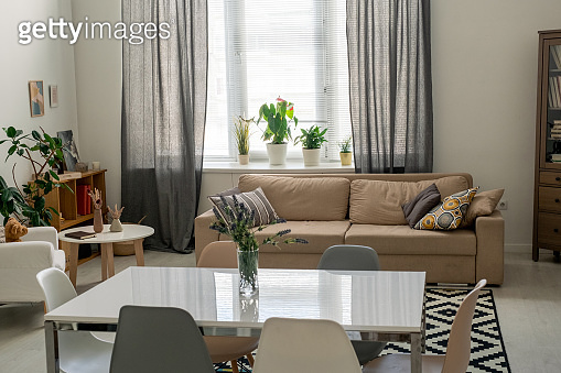 Interior of comfortable domestic room in flat or house with table in the center