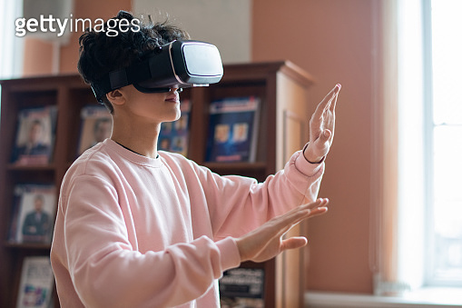 Mobile college student in casualwear and vr goggles touching virtual screen