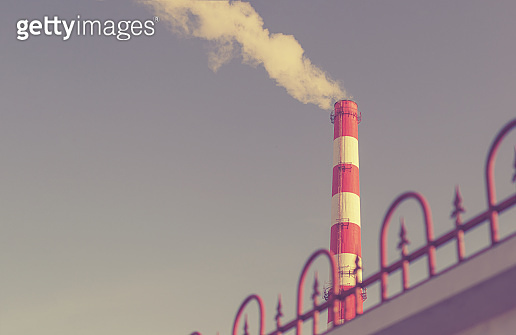 The factory chimney emits a blue poisonous smoke