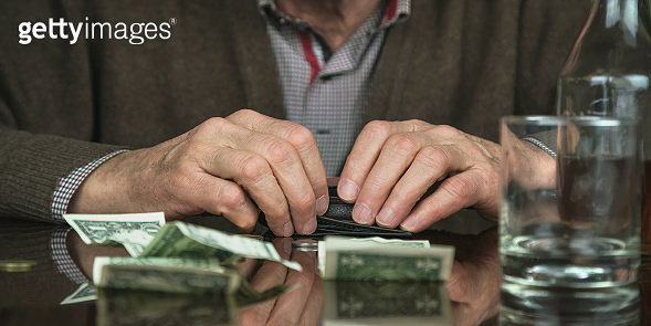 retired man holds hands on wallet sitting at table with banknotes and cognac bottle