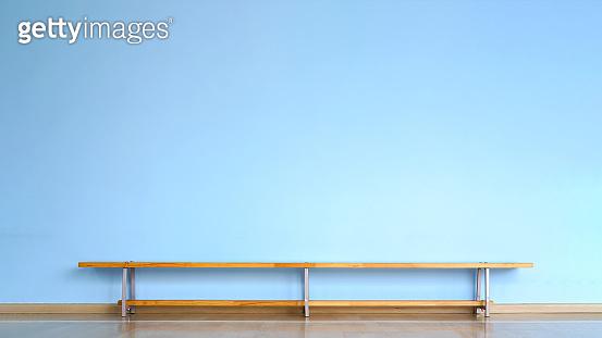 wooden bench stands on floor in empty room