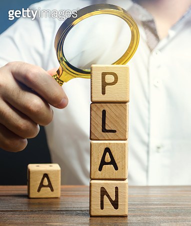 Wooden blocks with the word Plan and magnifying glass in the hands of a businessman. Strategy planning. Management business concept. Improving the efficiency of the company's sales. Financial target