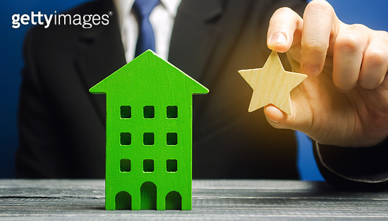 Businessman holds one star near the house. The concept of getting a star by a hotel. Improving the quality of service. Review and evaluation critic. Rise of the rating, a sign of quality.