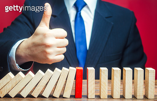 A businessman shows a thumbs up approval over a stopped process falling domino. Find a way stop the problem and prevent its spread. Achieving success and completing a task. Solution. Cyber protection