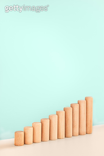Growth bar chart, graph diagram made with wooden block on blue background and copy space. Vertical orientation
