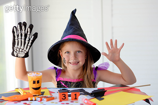 A little girl in a witch costume looks at the camera and scares.
