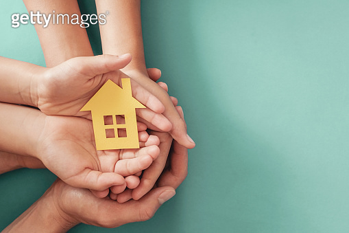Hands holding yellow paper house on blue background, family home, homeless shelter housing and home protecting insurance, mortgage concept, foster home care